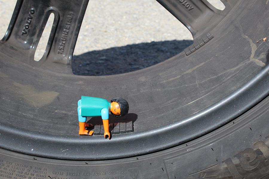 Playmobilmännchen sitzt gebeugt im Rahmen eines Autoreifens