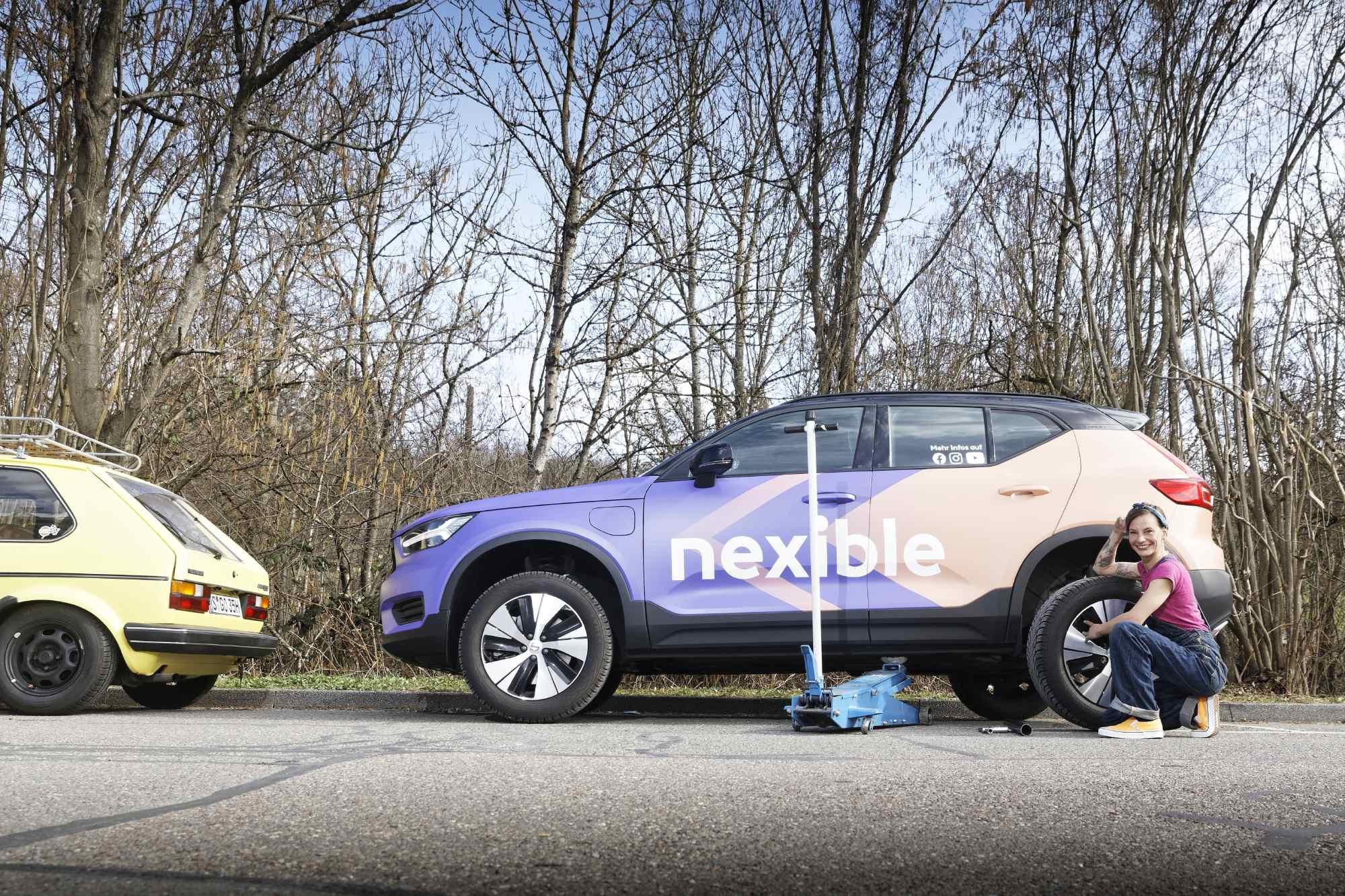 Automechanikerin Anna mit Wagenheber vor dem nexible-Auto nexiCar