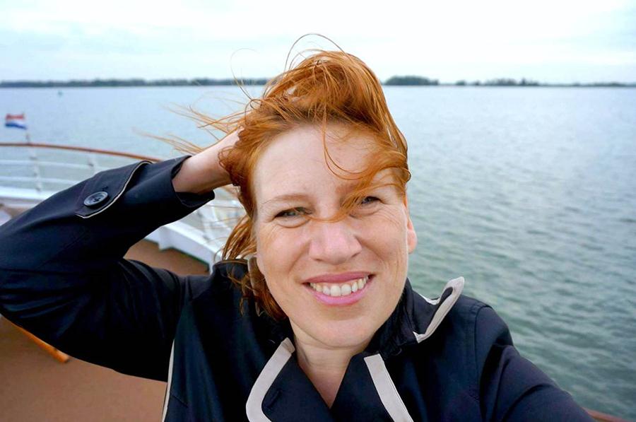 Selfie einer jungen Frau vor dem Meer bei Wind