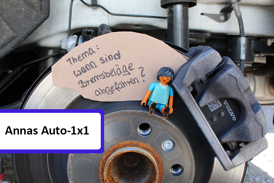 """Playmobilmännchen sitzt auf einer Bremsschreibe neben Schild, auf dem steht """"wann sind Bremsbeläge abgefahren"""""""