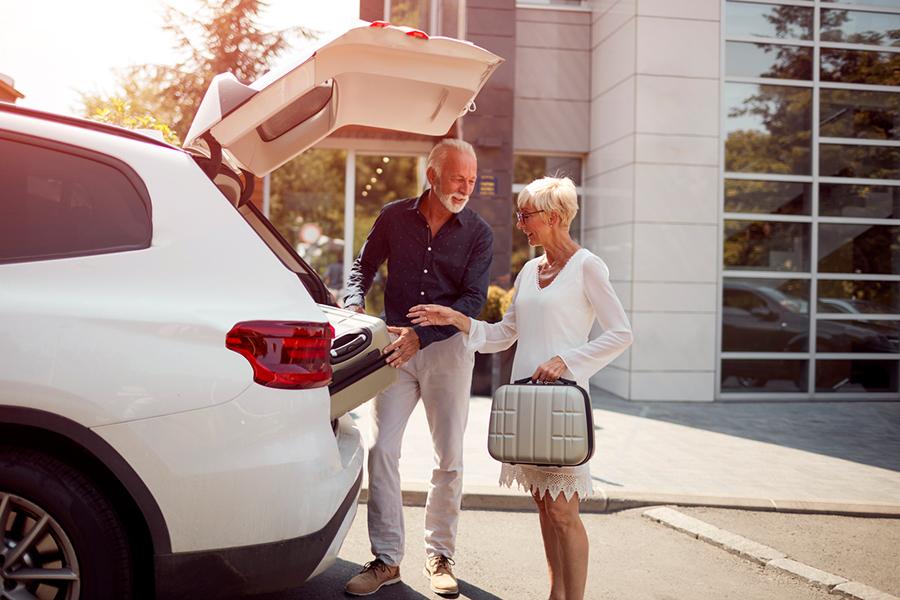 Älteres Paar steht vor offenem Kofferraum und packt Koffer ein