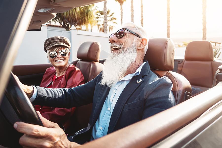 Senior und Seniorin gut gelaunt im Cabrio unterwegs